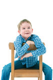 Cheerful boy sitting on a chair Royalty Free Stock Image