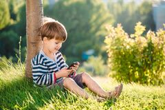 Cheerful boy sitting on the grass looks cartoons in the phone in the summer at sunset. Cute baby having fun in nature