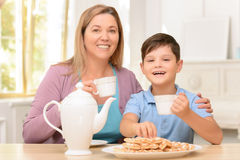Cheerful boy sitting in the kitchen Royalty Free Stock Photos