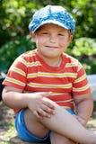 Cheerful boy sitting on a stump Stock Photo