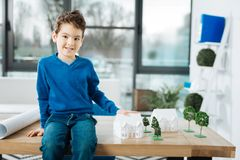 Cheerful boy sitting on table and touching house model. Future architect. Cute little boy posing for the camera while sitting on the table in the office and Royalty Free Stock Photos