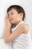 Cheerful boy sleep in bed. Cheerful boy sleep in white bed Royalty Free Stock Images