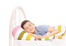 Cheerful boy sleeping in a comfortable bed. Cheerful little boy sleeping in a comfortable bed and dreaming sweet dreams covered with a blanket isolated on white Stock Photos