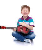 Cheerful boy in a striped t-shirt plays guitar Stock Photos