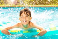 Cheerful boy swimming on air mattress in pool stock images