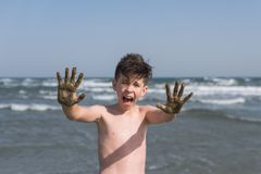Cheerful boy teenager shows his hands in the healing healing mud from the sea. Travel concept stock image