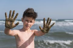 Cheerful boy teenager shows his hands in the healing healing mud from the sea. Travel concept stock photo