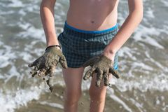 Cheerful boy teenager shows his hands in the healing healing mud from the sea. Concept royalty free stock photography