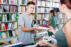 Cheerful boy teenager taking new book from seller Royalty Free Stock Image