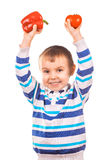 Cheerful boy with tomato and pepper on the white Royalty Free Stock Photo