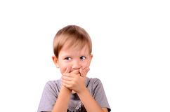 Cheerful boy 5 years shut by the hands mouth. Horizontal Image isolated on white background Stock Photo