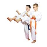Cheerful boys athletes train beat blows kicks Stock Images