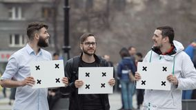 Cheerful boys talk in the city at rally and smile. Place your text on the banner. People at the demonstration with banners in their hands look into camera and