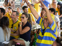 Cheerful Brazil Fans Watching World Cup Football Match on TV at a Bar royalty free stock images