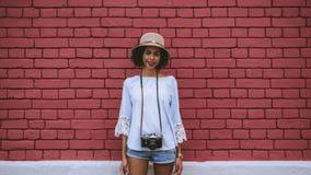 Cheerful Brazilian girl tourist near brick wall royalty free stock photography
