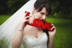 Cheerful bride bites the wooden letters of red Stock Photo