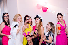 Cheerful bride and bridesmaids celebrating hen party with drinks Royalty Free Stock Photography