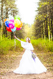 Cheerful bride with bunch of balloons outdoor Stock Images