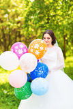 Cheerful bride  with bunch of balloons Royalty Free Stock Image