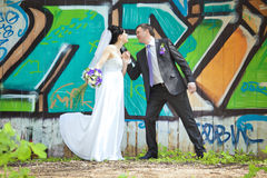 Cheerful bride and groom holding hands on graffiti wall Royalty Free Stock Photo