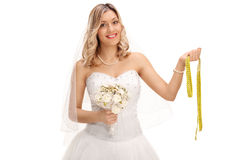 Cheerful bride holding a measuring tape Stock Image