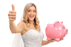 Cheerful bride making a thumb up sign and holding a piggybank Stock Images