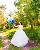 Cheerful bride  posing with bunch of balloons Royalty Free Stock Photos
