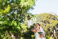 Cheerful bride throwing bouquet in park. Cheerful young beautiful bride throwing bouquet in the park Royalty Free Stock Image