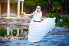Cheerful bride is walkingin the green park Royalty Free Stock Image