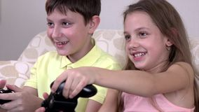 Cheerful brother and sister playing video games in the sofa at home. Pink shirt and a yellow T-shirt, big soft beige sofa, smiles of children stock video