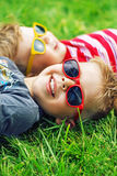 Cheerful brothers lying on the lawn Stock Photos