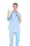 Cheerful brown haired nurse in blue scrubs giving a thumb up Stock Photos