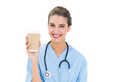 Cheerful brown haired nurse in blue scrubs holding a cup of coffee Stock Images