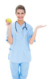 Cheerful brown haired nurse in blue scrubs holding a green apple Stock Photography