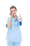 Cheerful brown haired nurse in blue scrubs making a phone call and raising her thumb Stock Photo