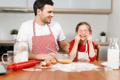 Cheerful brunet male wears apron looks at happy child who covers eyes with hearts, sit at wooden kitchen table, mixe stock images