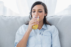 Cheerful brunette drinking orange juice Stock Photo