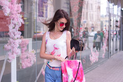 Cheerful brunette girl with bags smiles at the shopping center. Outdoors Royalty Free Stock Images