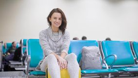 Cheerful brunette girl is sitting on bag in airport and waiting her flight, enjoying her future vacation and travel stock video