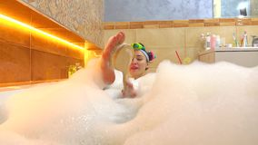 Cheerful brunette girl takes foamy bath and scrubs her foot with a brush. 4K shot stock footage