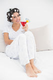 Cheerful brunette in hair curlers sitting on her bed holding a cocktail Stock Photography