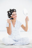 Cheerful brunette in hair rollers holding hand mirror and applyi Stock Photography