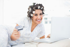 Cheerful brunette in hair rollers lying on her bed using her laptop to shop online Stock Image