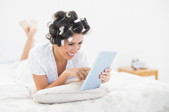 Cheerful brunette in hair rollers lying on her bed using her tab Stock Image
