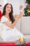 Cheerful brunette holding a bauble at christmas Royalty Free Stock Images