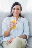 Cheerful brunette offering orange juice to camera Royalty Free Stock Images