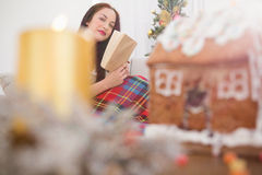 Cheerful brunette reading on the couch with cover at christmas Royalty Free Stock Photography
