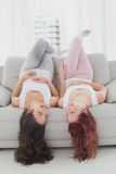 Cheerful brunette and redhead lying upside down on sofa in living room Stock Images