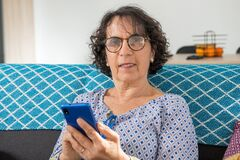 Free Cheerful Brunette Senior Woman Using Smartphone While Sitting On Sofa Royalty Free Stock Image - 173102136