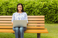Cheerful brunette sitting on bench using laptop Royalty Free Stock Photography